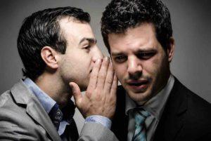 Mann spricht anderem Mann ins Ohr