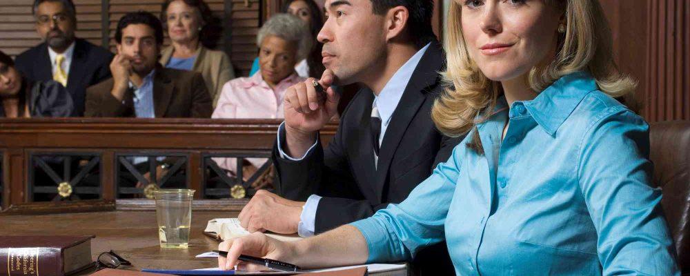 Verteiger sitzt mit Mandantin im Gerichtssaal